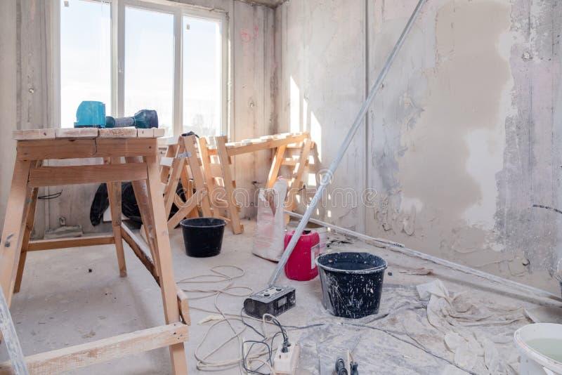 Деревянная стойка на окне в большой пустой комнате, ремонт лесов, штукатурящ, крася стены, инструменты здания, погань r стоковые фотографии rf