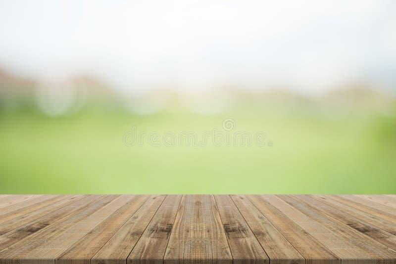 Деревянная столешница на предпосылке природы запачканной зеленым цветом стоковое изображение rf