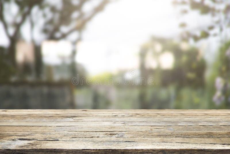 Деревянная столешница на запачканной предпосылке зеленого растения и сада - ca стоковая фотография