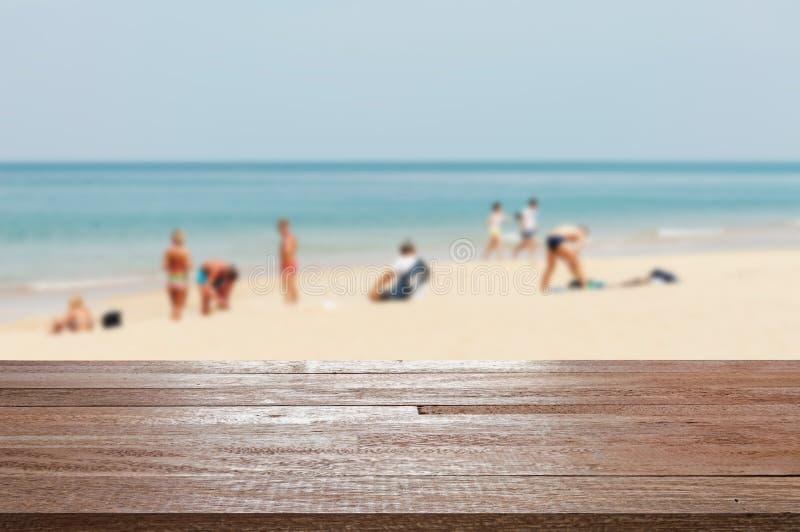 Деревянная столешница на запачканном голубом море и пляж с белым песком с сомом стоковое фото