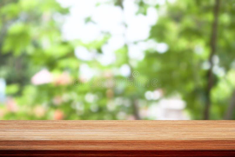 Деревянная столешница на зеленом цвете bokeh выходит предпосылка стоковое фото