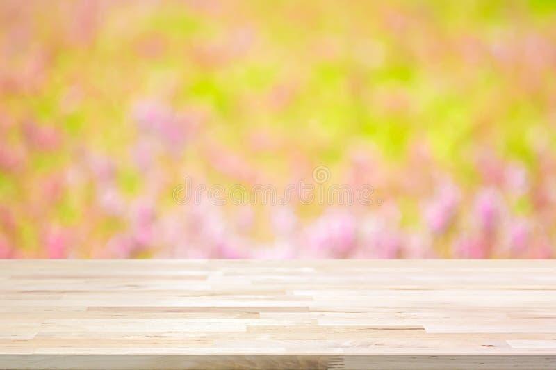 Деревянная столешница на предпосылке цветочного сада нерезкости стоковые фото