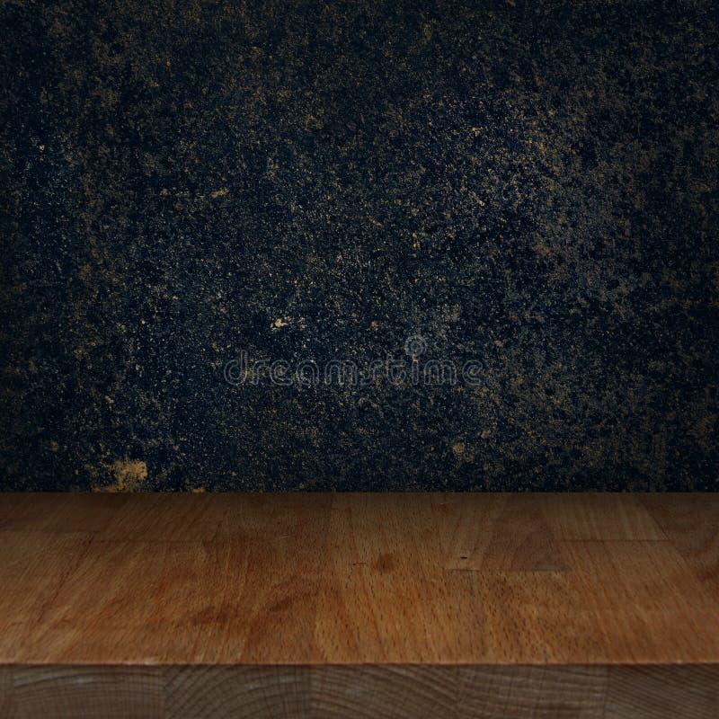 Деревянная таблица верхней части кухни с темной каменной предпосылкой стоковое изображение rf