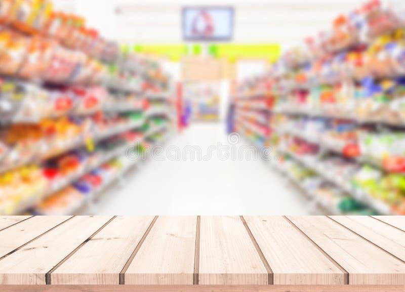 Деревянная таблица с предпосылкой нерезкости супермаркета для дисплея продукта стоковые фотографии rf