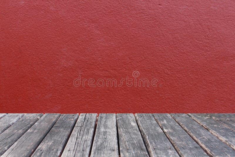 Деревянная таблица на красной предпосылке бетона стены стоковая фотография