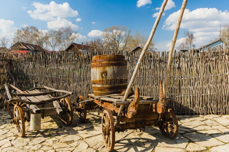 Деревянная тележка с бочонком около загородки стоковое фото rf