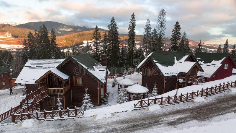 Деревянная хата покрытая с свежим снегом в древесинах в ландшафте в прикарпатских горах, Bukovel зимы, Украине стоковая фотография rf