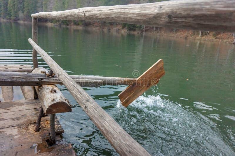 Деревянное домодельное весло, который гребут воду в озере стоковые изображения
