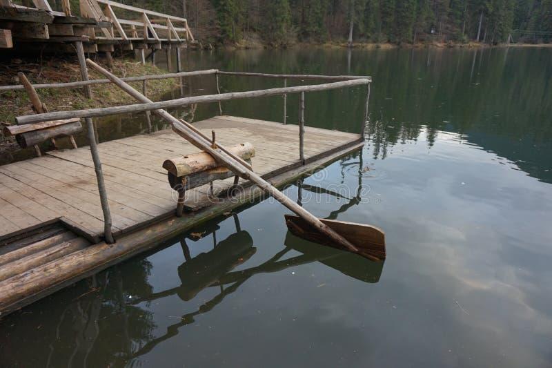 Деревянное домодельное весло, который гребут воду в озере стоковая фотография