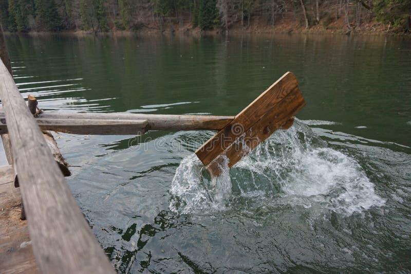 Деревянное домодельное весло, который гребут воду в озере стоковое фото rf