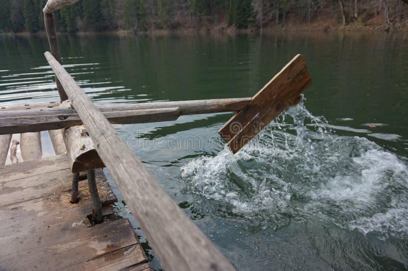 Деревянное домодельное весло, который гребут воду в озере стоковое изображение rf