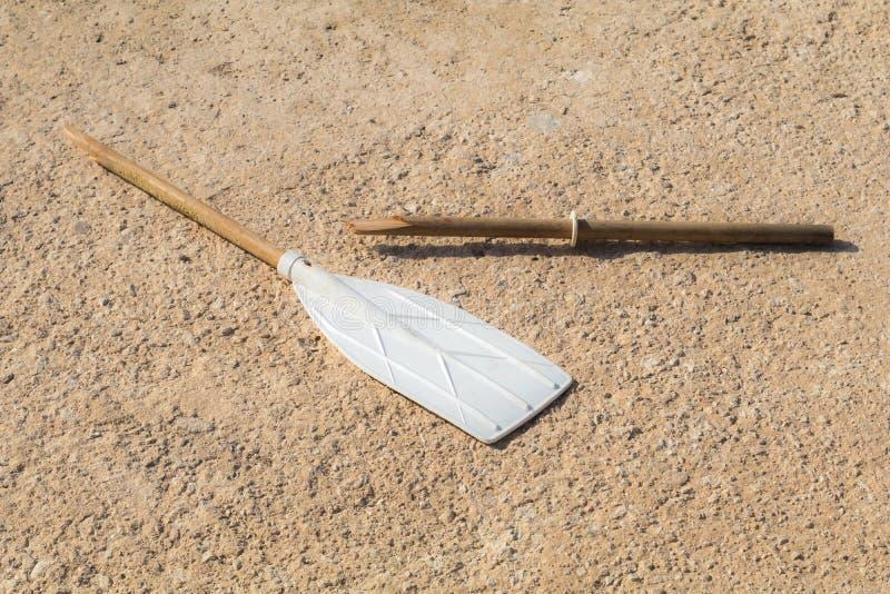 Деревянное сломанное весло, на tan бетоне, в солнце стоковое изображение