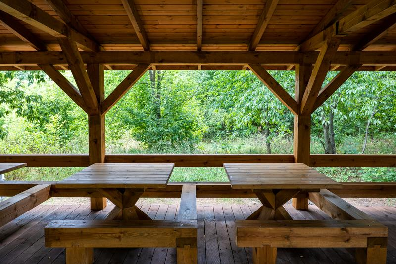 Деревянное укрытие с таблицами в парке стоковая фотография