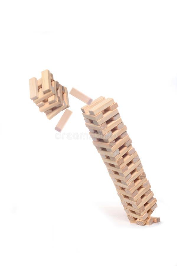 Деревянные блоки забавляются башня падая вниз изолированный на белой предпосылке с космосом экземпляра стоковая фотография