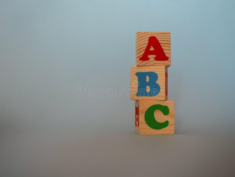 Деревянные блоки игрушки алфавита с текстом: abc Изолированные кубы ABC детей пестротканые на голубой предпосылке с космосом экзе стоковое фото rf