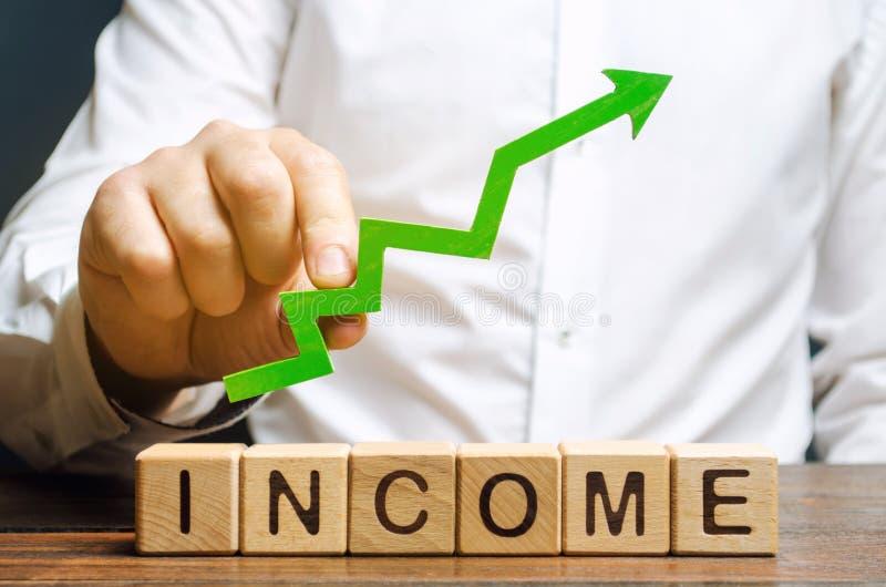 Деревянные блоки с доходом слова и поднимающая вверх стрелка в руках бизнесменов Концепция увеличивая выгод и финансов стоковые фото