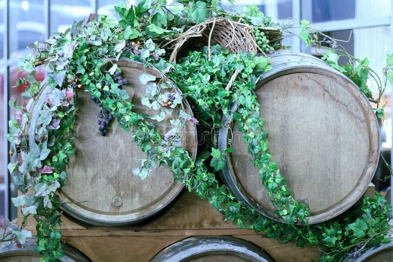 Деревянные бочонки вина для виноградников украшенных с листьями плюща и связками винограда стоковое фото