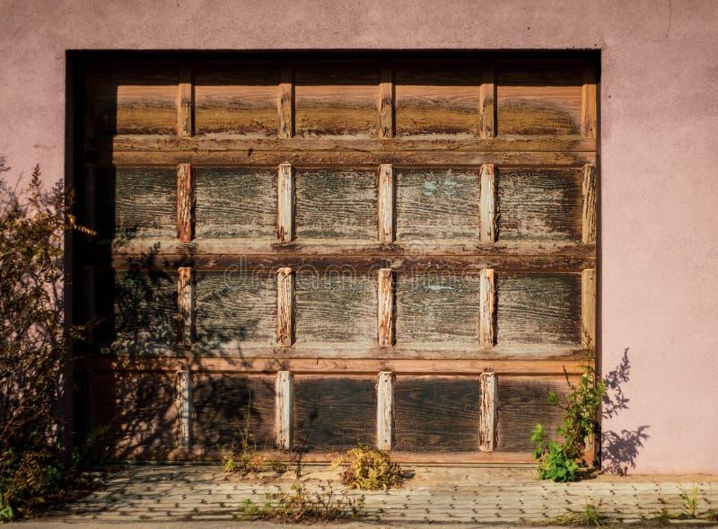 Деревянные ворота утюга к гаражу с розовыми стенами на ясный солнечный день Современная красивая автоматическая дверь стоковая фотография
