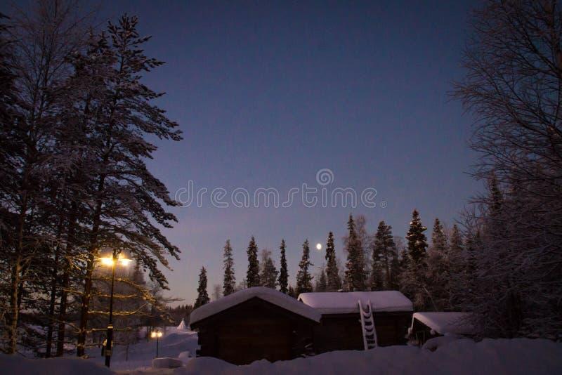 Деревянные дома в зиме на ноче стоковые фотографии rf