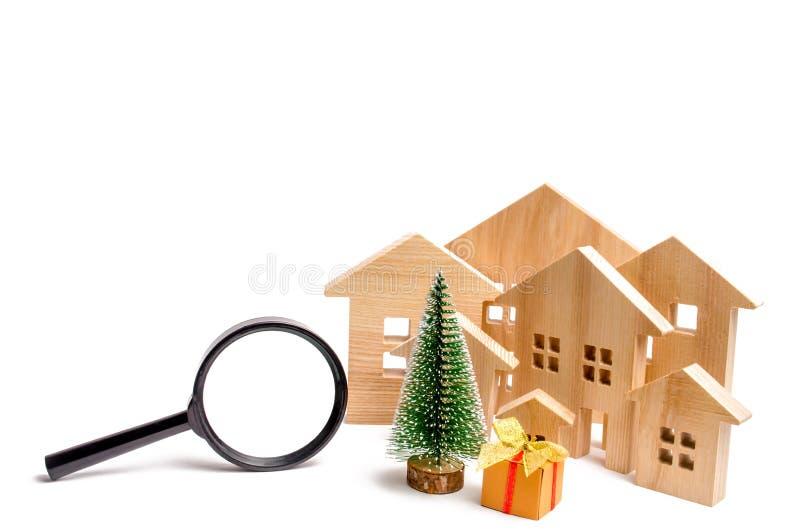 Деревянные дома и рождественская елка и лупа Концепция поиска гостиница или курорт на праздник Нового Года и стоковые фото