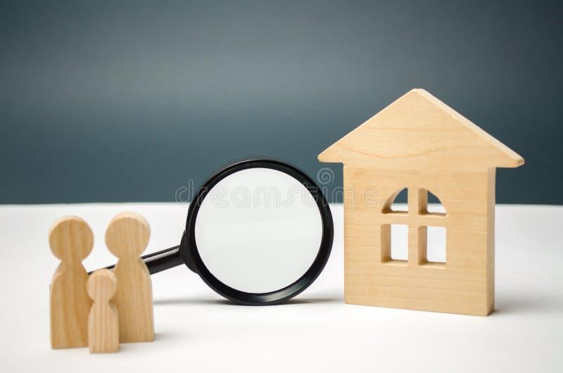 Деревянные дом и лупа с семьей Валюация свойства Выбор положения для конструкции Искать дома стоковые фотографии rf