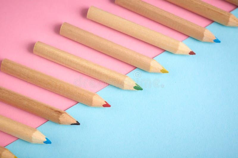 Деревянные карандаши цвета на голубой предпосылке, плоском положении стоковое изображение
