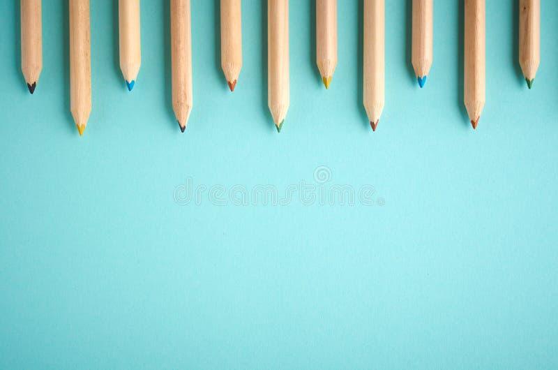 Деревянные карандаши цвета на голубой предпосылке, плоском положении стоковая фотография