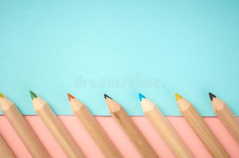 Деревянные карандаши цвета на голубой предпосылке, плоском положении стоковые фото