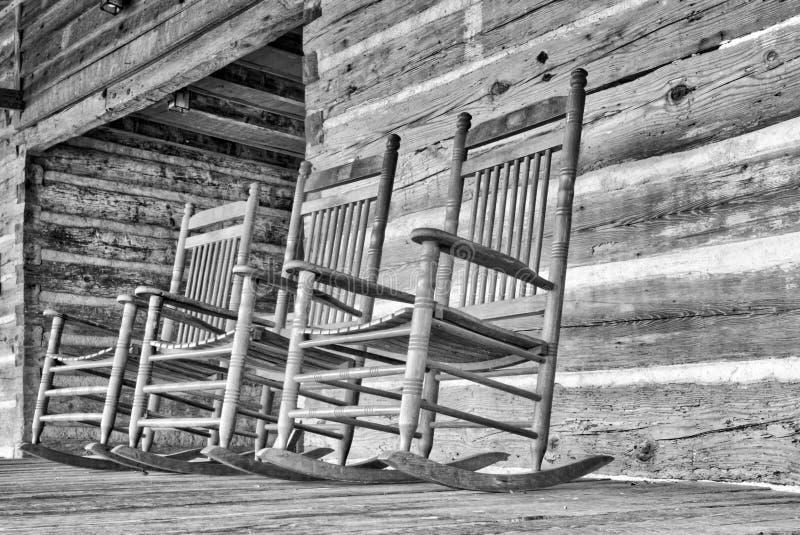 Деревянные кресло-качалки сидят бесполезное на крылечке стоковые фотографии rf