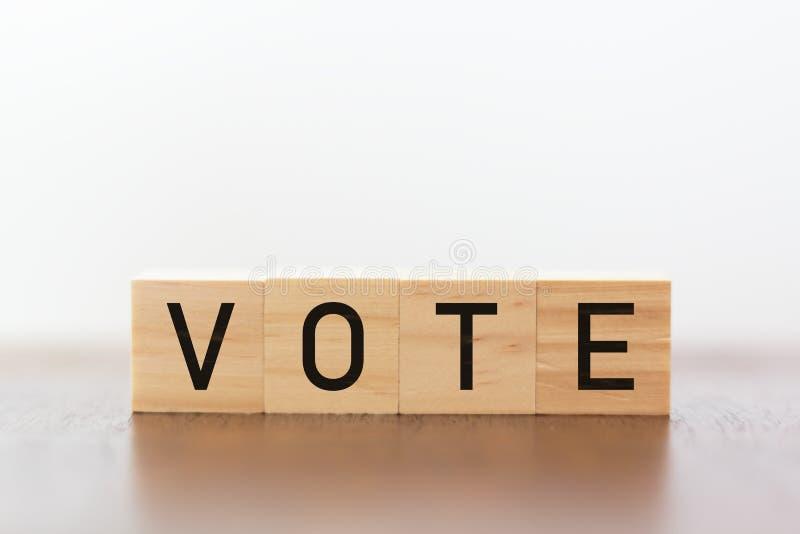 Деревянные кубы с голосованием написанным против белой предпосылки стоковые фотографии rf