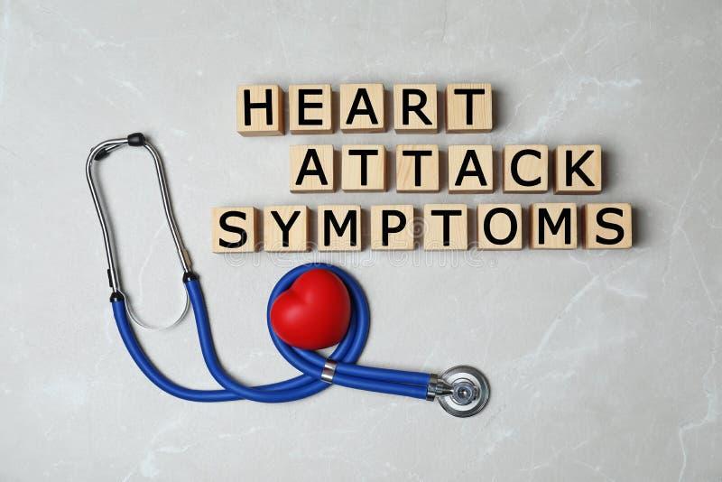 Деревянные кубы с симптомами сердечного приступа текста и стетоскоп на серой предпосылке стоковые изображения rf