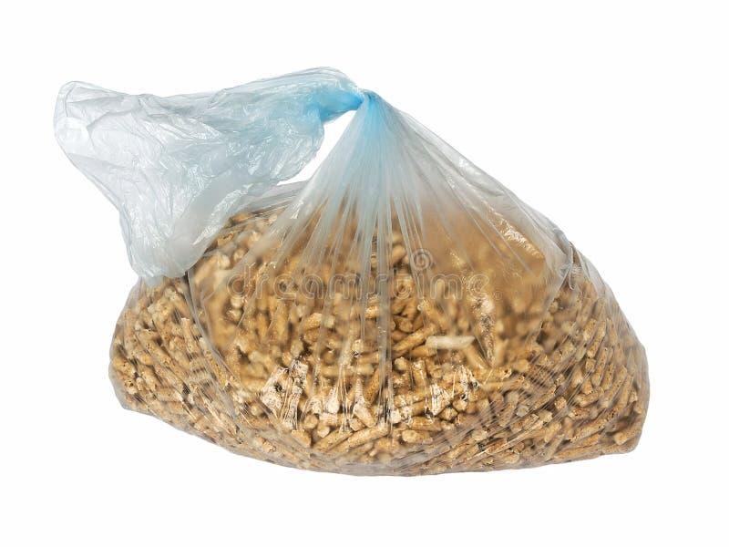 Деревянные лепешки в пластиковой сумке целлофана изолированной на белой предпосылке Альтернативное биотопливо от опилк для гореть стоковые фотографии rf