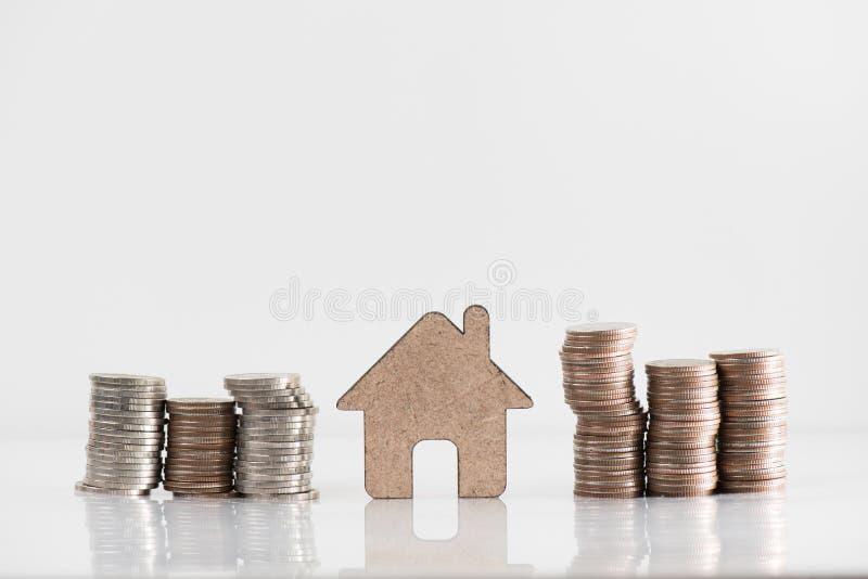 Деревянные модель дома и стог монетки иллюстрируют финансовые сбережения, h стоковые изображения rf