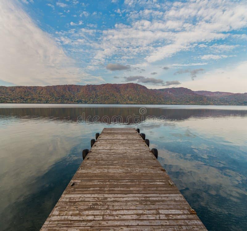 Деревянные пристань и озеро Towada в осени приправляют стоковое фото