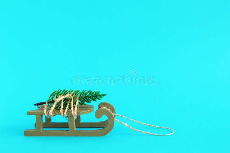 Деревянные сани со связанной искусственной елью на яркой голубой предпосылке Концепция рождества и Нового Года с космосом экземпл стоковое изображение