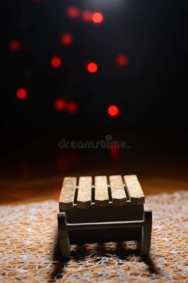 Деревянные сани с красными светами рождества на заднем плане стоковые фото