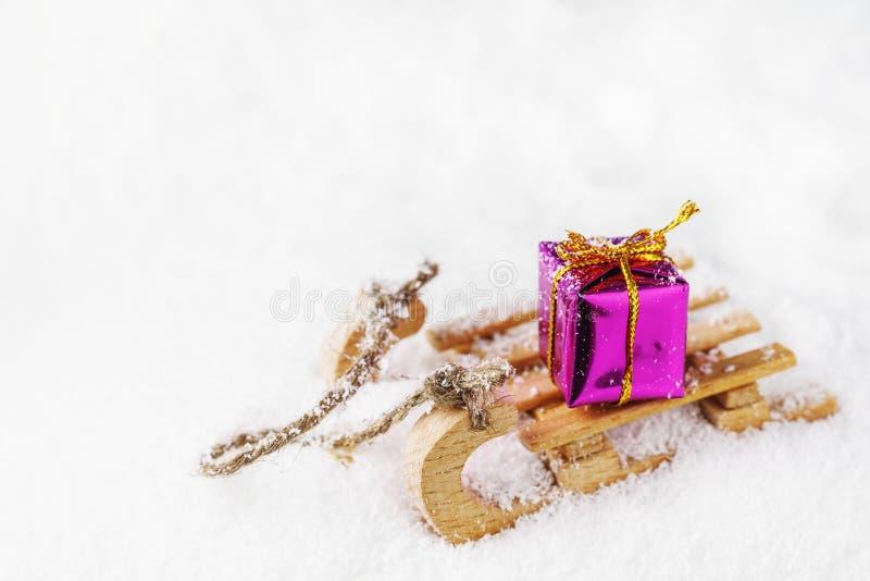 Деревянные сани с подарком на рождество на снеге стоковые фотографии rf