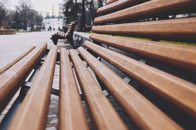 Деревянные скамьи Брауна сходятся к центру указывая в направлении красивого парка стоковые фотографии rf