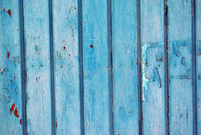 Деревянные старые дверь или строб покрашенные с голубой затрапезной краской и красными пятнами стоковая фотография rf