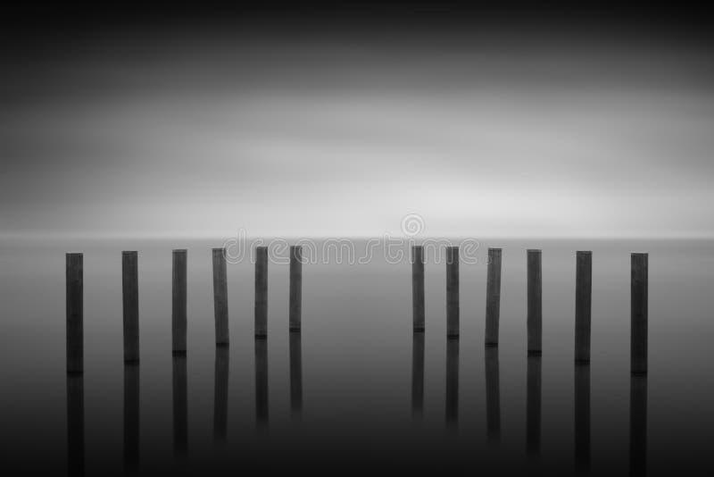 Деревянные столбы в озере, выдержка долгого времени стоковая фотография