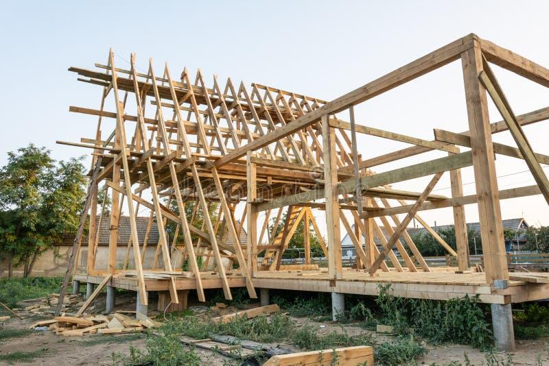 Деревянные стропилины нового дома под конструкцией на заходе солнца стоковые изображения rf