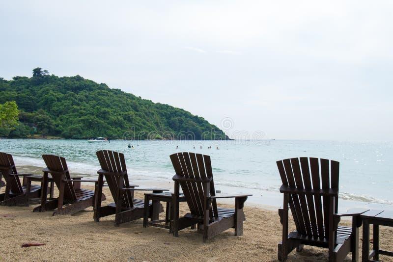 Деревянные стулья на каникулы и ослабляют на пляже стоковая фотография rf