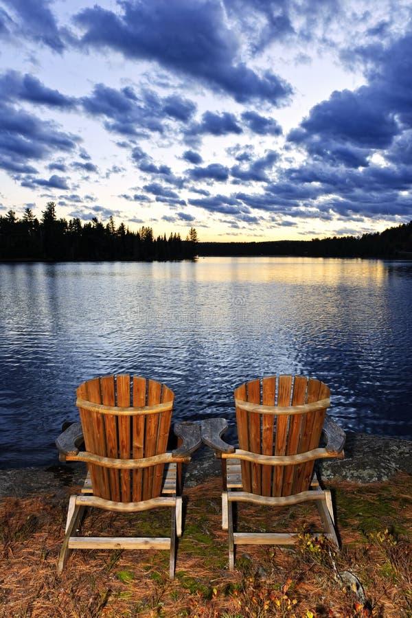 Деревянные стулья на заходе солнца на береге озера стоковые изображения rf
