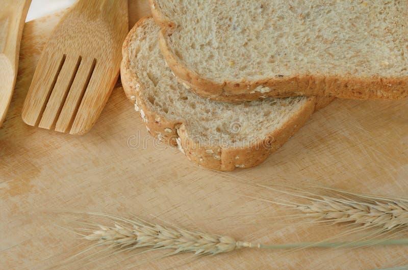 Деревянные утвари и пшеница кухни на деревянной предпосылке стоковая фотография