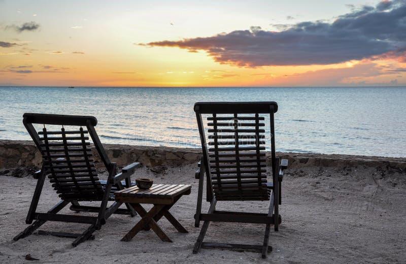 Деревянные шезлонги обозревая заход солнца на острове Holbox стоковые изображения