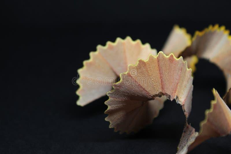 Деревянные Shavings карандаша на черной концепции предпосылки абстрактного искусства бумаги ремесла соответствующей для творчески стоковые фотографии rf