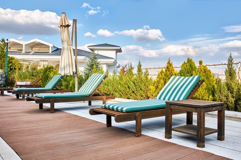 Деревянные sunbed шезлонги около на открытом воздухе poolside стоковая фотография rf