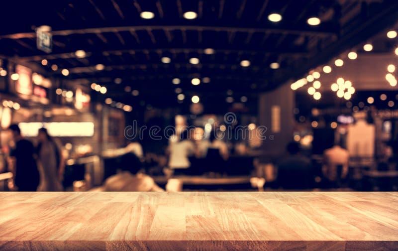 Деревянный бар столешницы с bokeh света нерезкости в темном кафе ночи стоковые фотографии rf