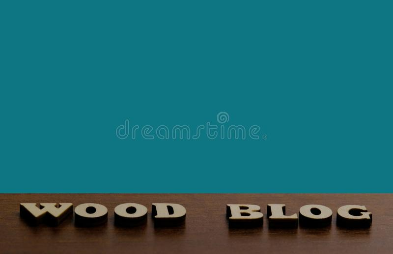 ДЕРЕВЯННЫЙ БЛОГ Надпись сделанная деревянных писем против текстуры древесины темного коричневого цвета Голубая предпосылка для ко стоковые фотографии rf