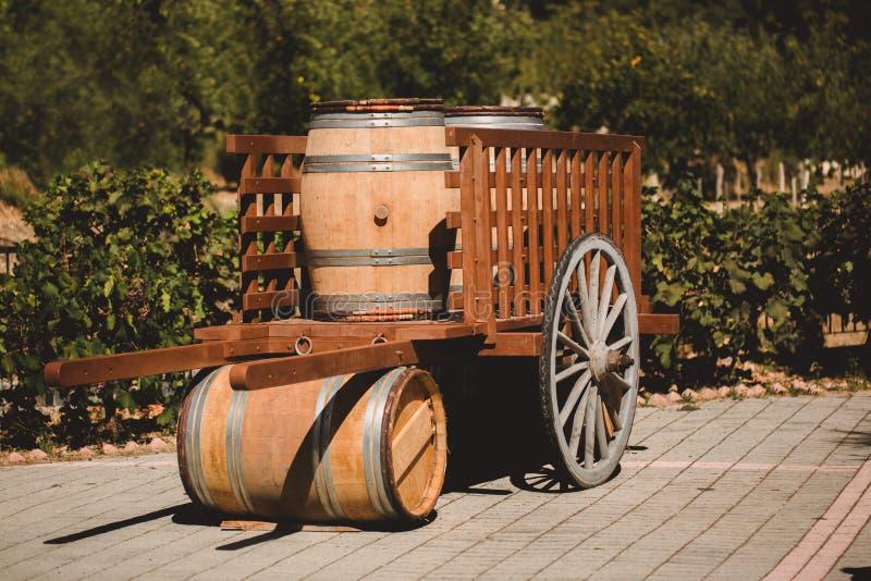 Деревянный бочонок с красным цветом и wihte wine для пробовать в тележке на винограднике Текстурированный объект стоковая фотография
